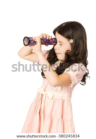 Little dark-haired girl in pink dress is passionately looking into a Kaleidoscope. Closeup - Isolated on white background - stock photo