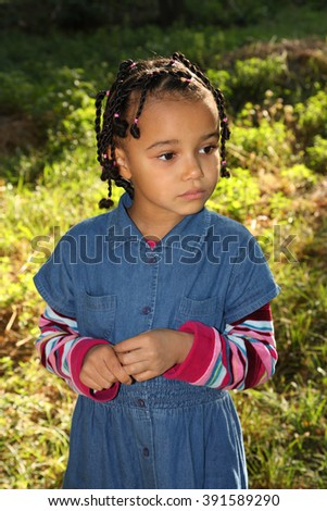 Little dark-skinned girl standing on the grass and looks toward