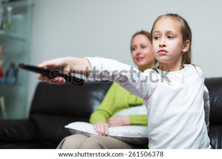Little daughter and mom in front of TV at home - stock photo