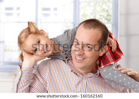 Little daughter around father's neck having fun, both laughing. - stock photo