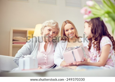 Little daughter giving surprise to her mother and grandmother - stock photo