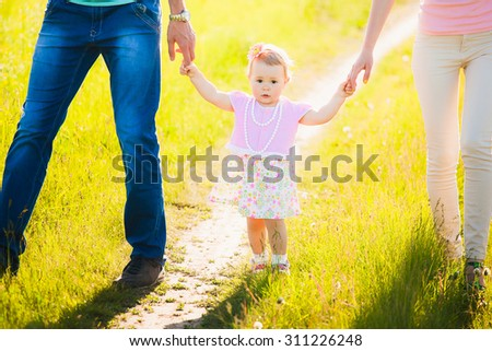 Little daughter holding hands of mom and dad. Portrait of happy family. - stock photo