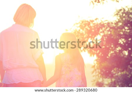 Little daughter looking at her mother, holding her hand when backlit sunset light. Vintage Family composition