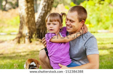 Little daughter on her father hands spend time in the park - stock photo