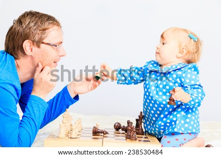 little daughter playing chess with father indoors - stock photo