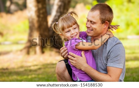 Little daughter playing with her father on the green meadow in park - stock photo