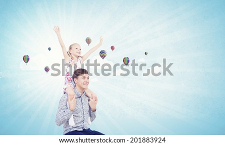 Little daughter sitting on father's shoulders. Parenting concept - stock photo
