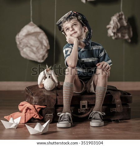 Little daydreamer sitting on suitcase and dreaming about diving - stock photo