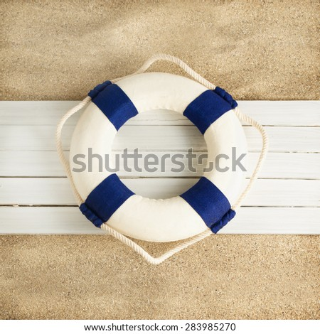 Little decorative lifebuoy on a wooden planks over sandy background. - stock photo