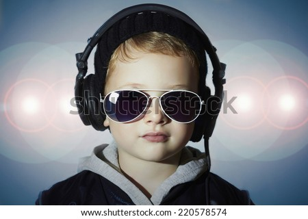 little deejay. funny boy in sunglasses and headphones.child listening music in headphones. DJ in disco lights - stock photo