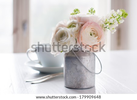 Little delicate elegant bouquet of flowers, buttercups and white lilacs in tin can and a teacup on white wooden table, morning breakfast - stock photo