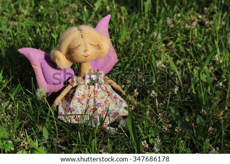 Little delicate handmade textile doll girl butterfly with closed eyes white hair and purple wings on grass