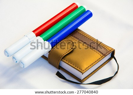 Little diary book with color markers  - stock photo