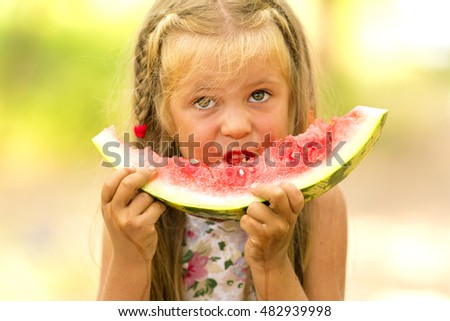 Little dirty blond girl eating a slice of red watermelon on blurred background