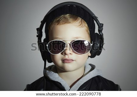 little DJ. funny boy in sunglasses and headphones.child listening music. deejay.gray background - stock photo