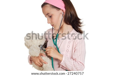 Little doctor examining her teddy bear on a over white background - stock photo