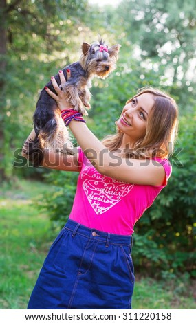 Little dog with owner spend a day at the park playing and having fun - stock photo