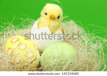 Little Easter basket with eggs and chicken on a green background