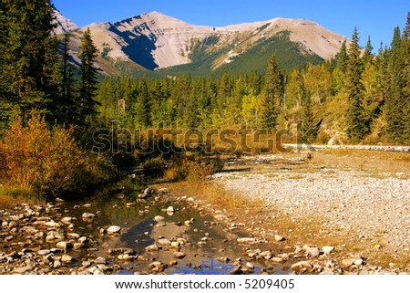 Little Elbow River Valley, Kananaskis country, Alberta, Canada (near Calgary); early autumn colours, along river; mountains; crisp clear day; blue skies - stock photo