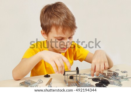 Little engineer plays with mechanical starter kit at the table