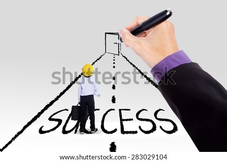 Little engineer standing on a road with a success text and a hand drawing a door at the end of the road - stock photo
