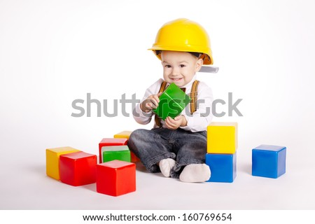 little engineer with protective helmet plays with cubes