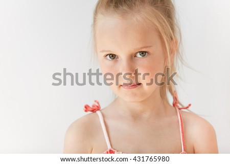 Little European girl in summer dress posing on white background. Pretty child with big green eyes and messy blond hair standing with serious facial expression. - stock photo