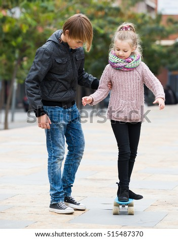 Little european girl learning to ride skateboard, teenage brother supporting her