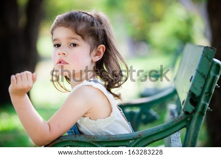 Little European girl sit on the chair in the garden