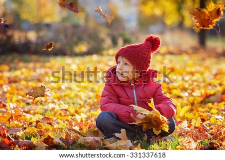 Little excited boy playing with leaves in the park, autumn time