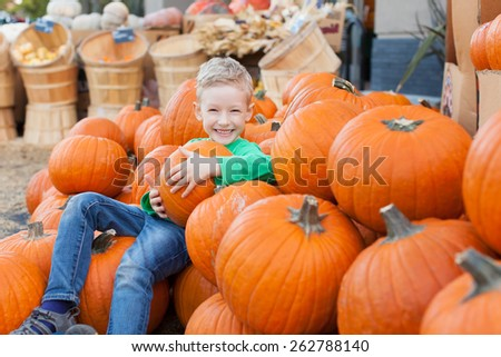 little excited kid enjoying time at pumpkin patch sitting in the huge pile of pumpkins - stock photo
