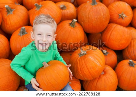 little excited kid looking up enjoying time at pumpkin patch sitting in the huge pile of pumpkins - stock photo