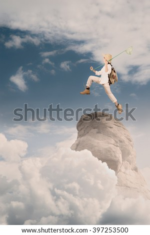 little explorer holding a butterfly net on a mountain - stock photo