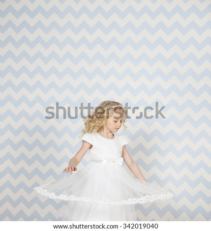 Little fairy angel in white fashion dress smiling in motion. Blue background.  Copy space  - stock photo