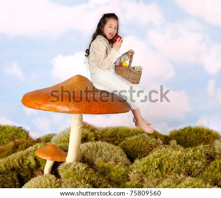 Little fairy child sitting on a toadstool eating an apple - stock photo