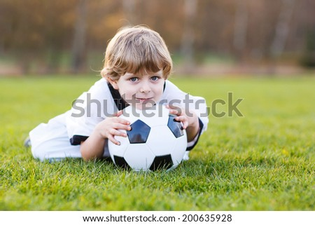 Little fan boy at public viewing of soccer or football game, outdoors - stock photo