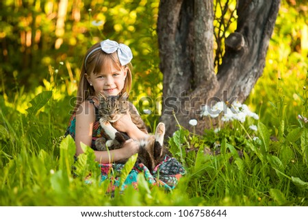 Little fanny girl playing with a cat in the park - stock photo