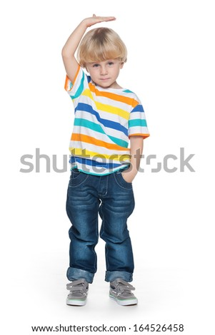 Little fashion boy shows his height - stock photo