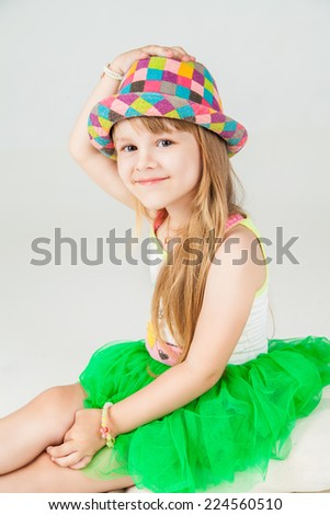 Little fashion girl in beautiful dress and hat posing over white background - stock photo