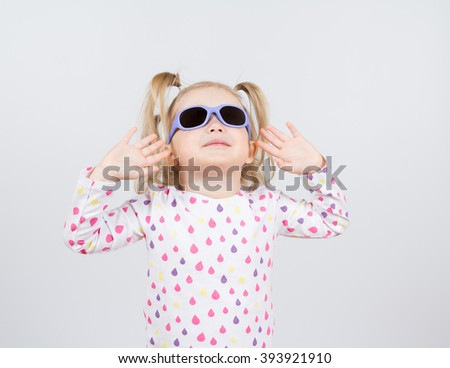 Little fashion girl in sunglasses on a white background.