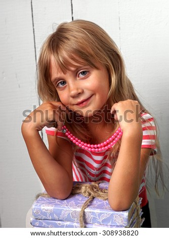 Little fashion girl with beads  posing over white background.                   - stock photo