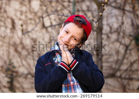 Little fashionable boy in red cap at spring, outdoor portrait - stock photo