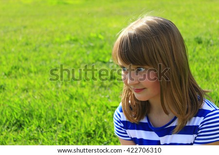 little fashionable girl smirks on the green grass background