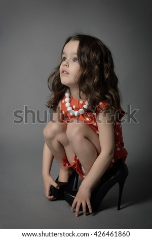 Little fashionista. Little beautiful fashion girl posing in mother's high heels shoes and happy smiling. - stock photo
