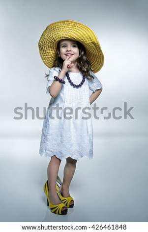 Little fashionista. Little beautiful fashion girl posing white dress, mother's high heels shoes and panama hat. Summer fashion. - stock photo