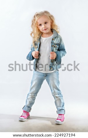 Little fashionista posing in denim suit against white background