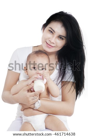 Little female baby drinking milk from the bottle with her mother, isolated on white background
