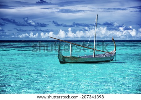 Little fishing boat in blue sea, beautiful peaceful seascape background, clear transparent water of Maldives islands - stock photo