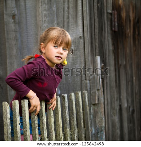 Little five-year girl and vintage rural fence. - stock photo