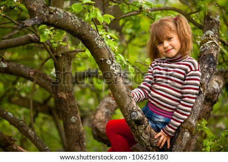 Little five-year girl posing sitting on a tree in the garden. - stock photo